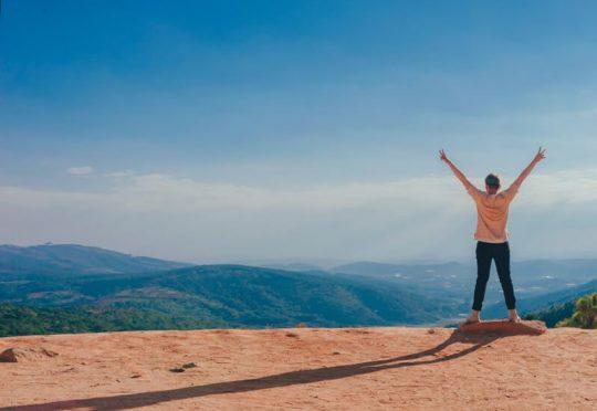 imagen de persona en lo alto de una montaña. superando momentos de fristeza