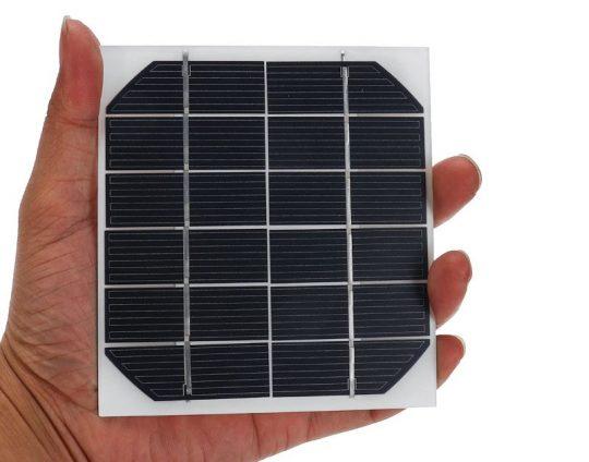 imagen de una célula fotovoltaica de un panel solar asida en una mano humana a modo de comparación de tamaño