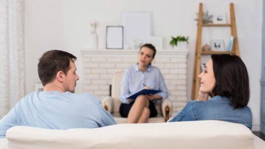 imagen en la que aparece una experta en terapias de pareja al fondo y de espaldas una pareja de hombre y mujer